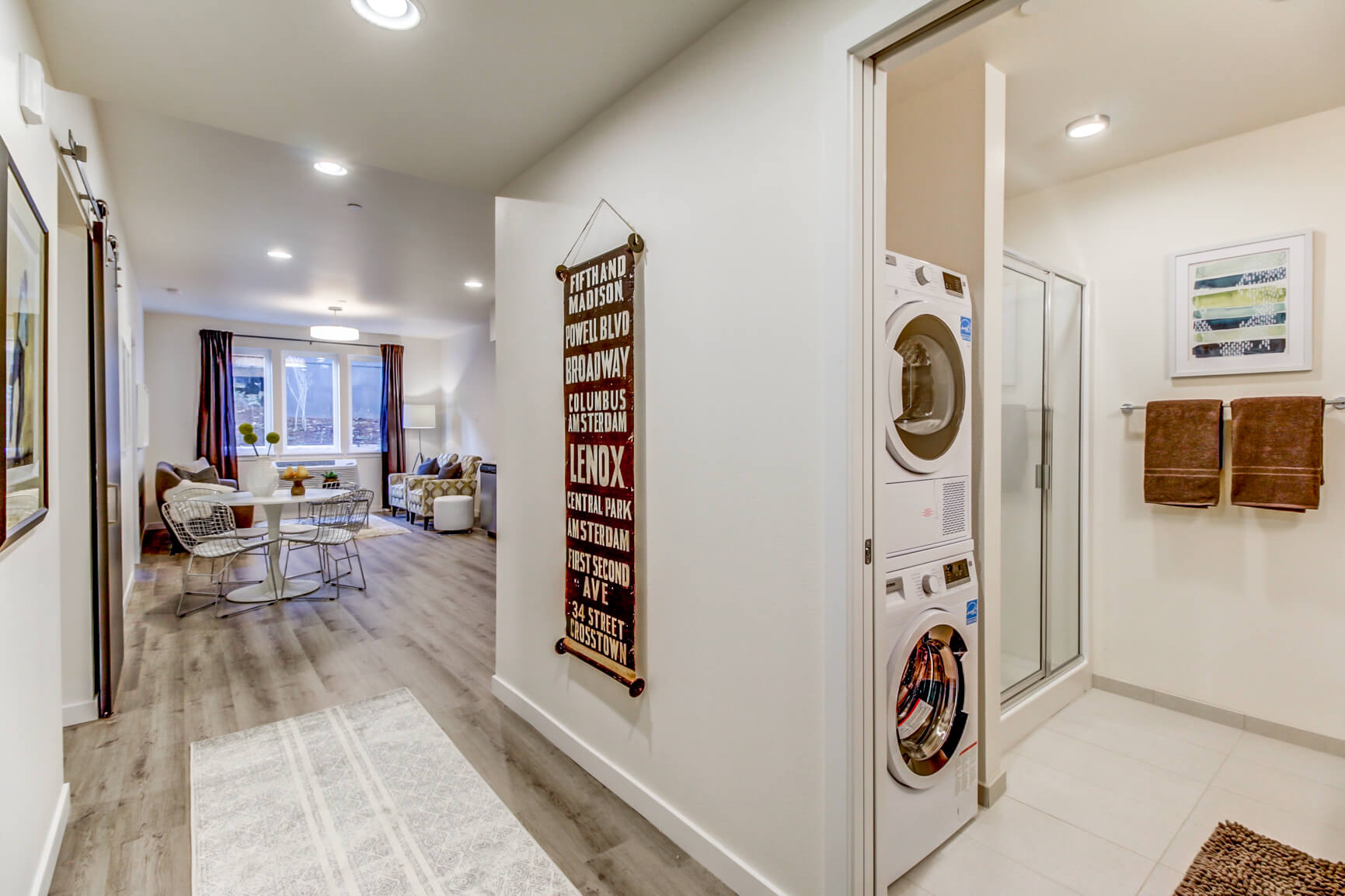 Hallway with view of washer dryer and shower